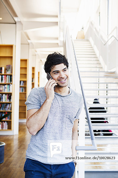 Happy young man communicating on cell phone while standing by steps in library