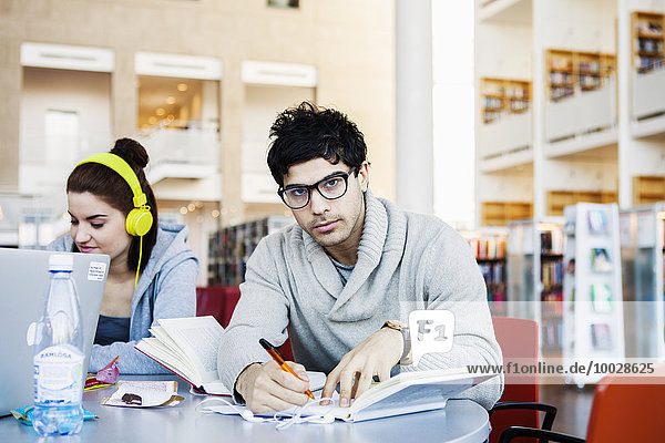 Portrait of confident young man writing notes while sitting in library