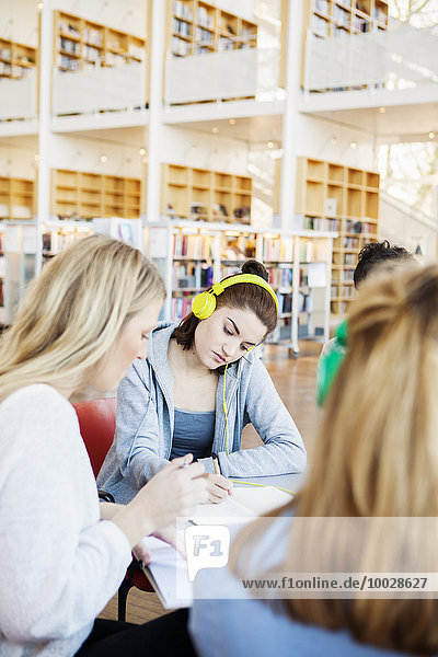 Woman wearing headphones while sitting with friends in library
