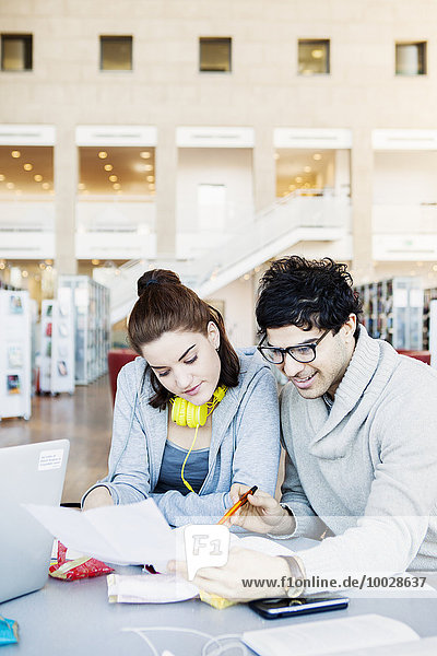 Smiling young man reading document with friend at table in library