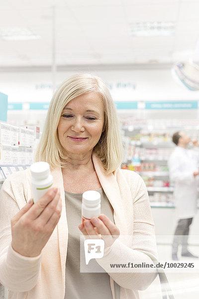 Kunden lesen Etiketten auf Flaschen in der Apotheke
