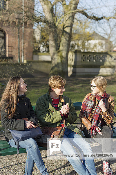 Teenage friends talking while sitting on bench in college campus