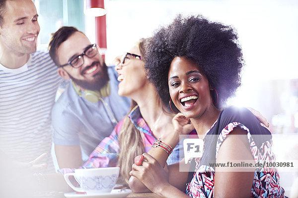 Porträt einer lachenden Frau  die mit Freunden im Café rumhängt.
