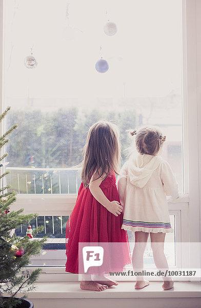 Mädchen auf Fensterbank unter Weihnachtsschmuck