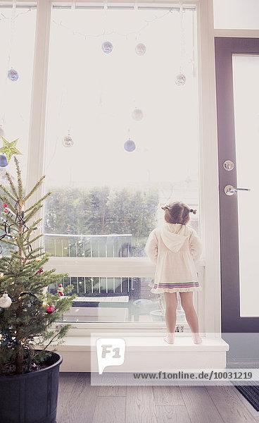 Neugieriges Mädchen auf Fensterbank unter dem Weihnachtsschmuck