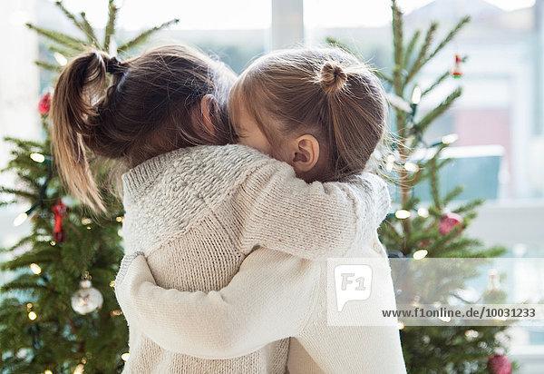 Mädchen umarmen sich vor Weihnachtsbäumen