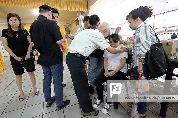 Relatives consoling the grieving widow. Sarawakian chinese funeral ceremony. Malaysia