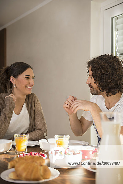 Mid adult couple talking at breakfast table  Munich  Bavaria  Germany