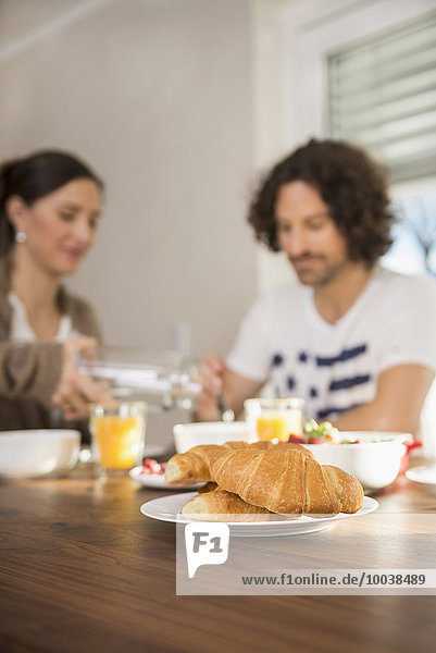 Croissants on dining table and mid adult couple having breakfast in the background  Munich  Bavaria  Germany