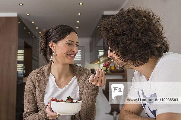 Mid adult woman feeding a strawberry to her husband  Munich  Bavaria  Germany