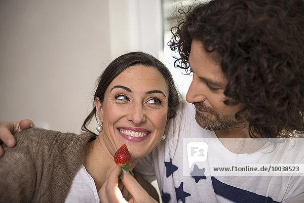 Mid adult man feeding a strawberry to his wife  Munich  Bavaria  Germany
