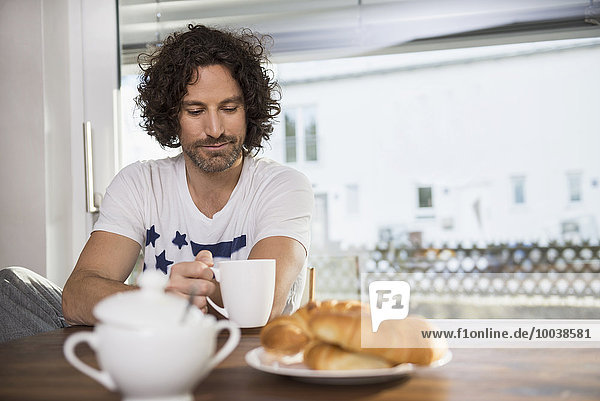 Mid adult man drinking cup of coffee at breakfast table  Munich  Bavaria  Germany Mid adult man drinking cup of coffee at breakfast table, Munich, Bavaria, Germany