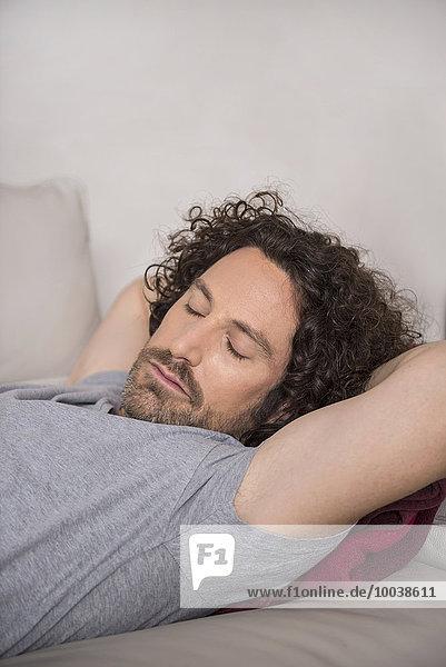 Mid adult man sleeping on couch  Munich  Bavaria  Germany