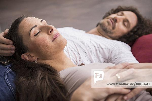 Mid adult couple sleeping on floor  Munich  Bavaria  Germany