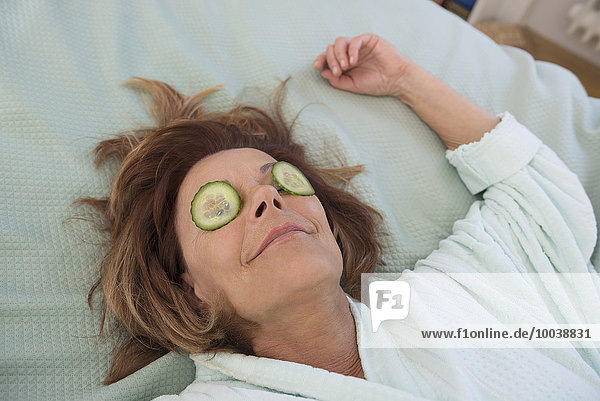 Senior woman with cucumber slices on her eyes  Munich  Bavaria  Germany