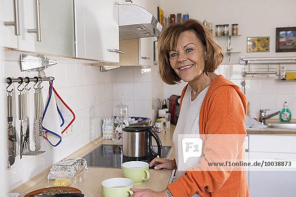 Senior woman preparing tea in the kitchen  Munich  Bavaria  Germany