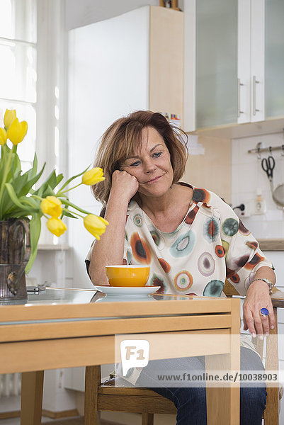 Senior woman in deep thought while having tea in the kitchen  Munich  Bavaria  Germany