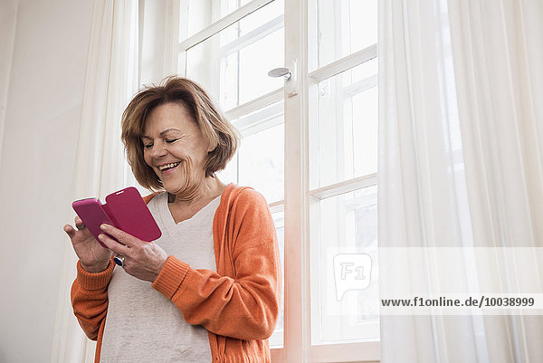 Happy senior woman text messaging on a smart phone by window  Munich  Bavaria  Germany
