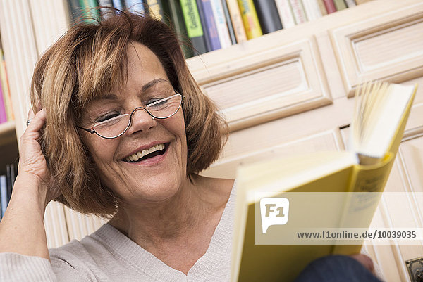 Senior woman while reading in front of bookshelf  Munich  Bavaria  Germany