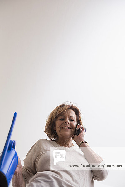 Happy senior woman talking on mobile phone and holding a watering can  Munich  Bavaria  Germany