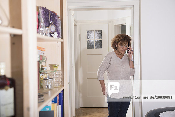 Senior woman talking on mobile phone at doorway  Munich  Bavaria  Germany