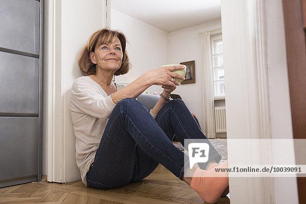 Senior woman having cup of tea at doorway  Munich  Bavaria  Germany