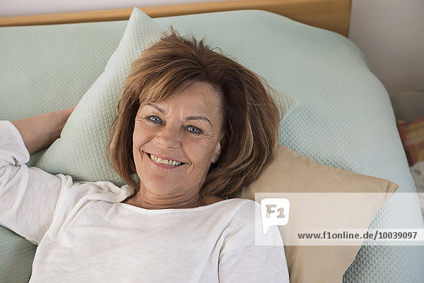 Portrait of senior woman lying on bed and smiling  Munich  Bavaria  Germany