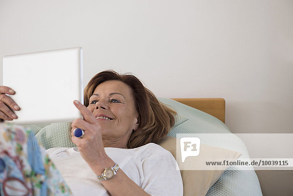 Senior woman lying on bed and using a digital tablet  Munich  Bavaria  Germany