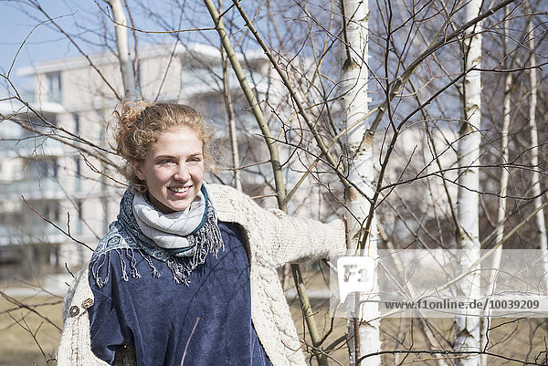 Young woman playing with birch tree  Munich  Bavaria  Germany