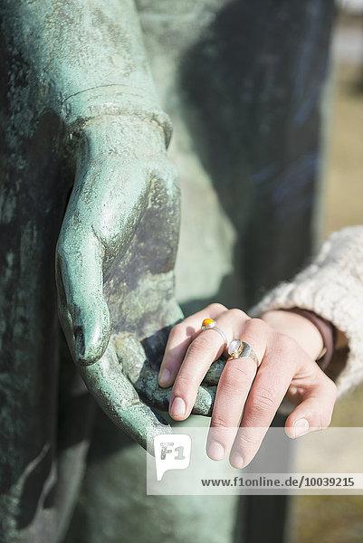 Woman touching hand of bronze sculpture  Munich  Bavaria  Germany Woman touching hand of bronze sculpture, Munich, Bavaria, Germany