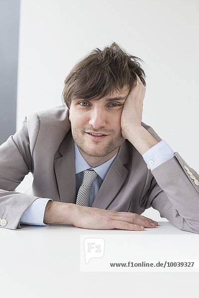 Businessman leaning on desk in office  Leipzig  Saxony  Germany