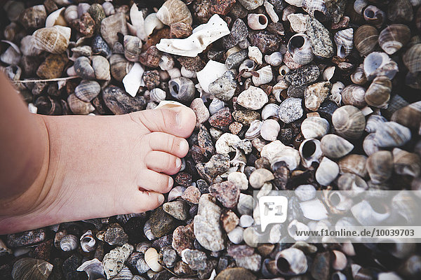 Childs foot on beach  close-up