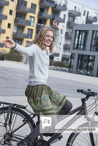 Young woman performing stunt on bicycle  Munich  Bavaria  Germany