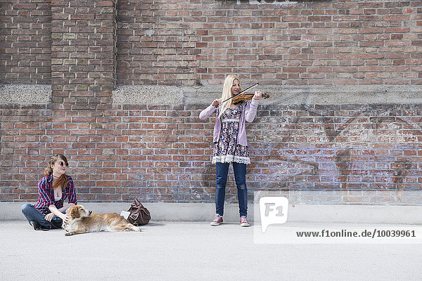 Woman sitting with her friend playing violin in front of brick wall  Munich  Bavaria  Germany