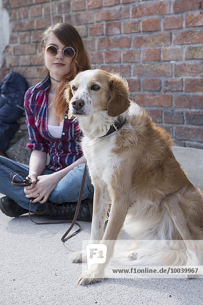 Young woman with dog in front of brick wall  Munich  Bavaria  Germany