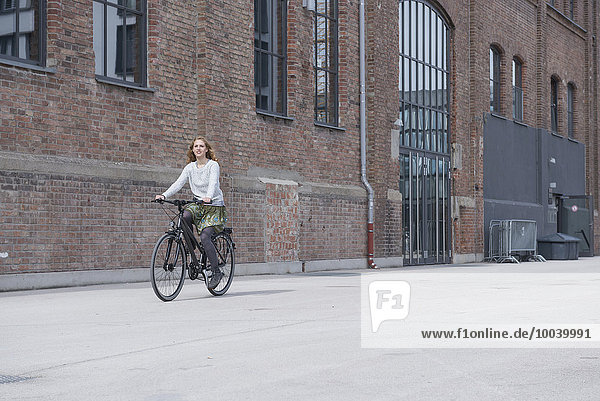 Young woman riding a bicycle in front of brick wall  Munich  Bavaria  Germany