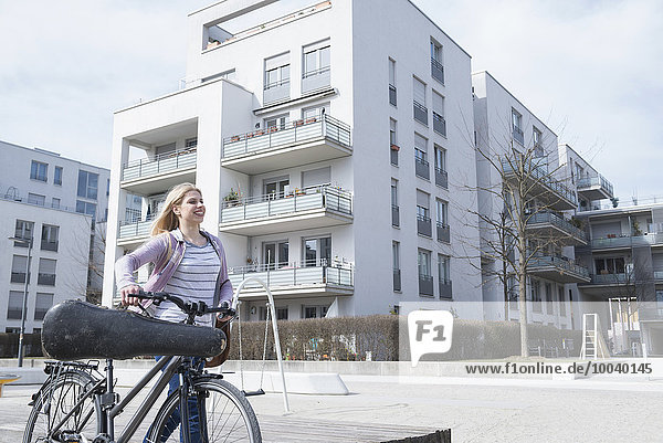 Teenage girl walking in city with bicycle and violin case  Munich  Bavaria  Germany