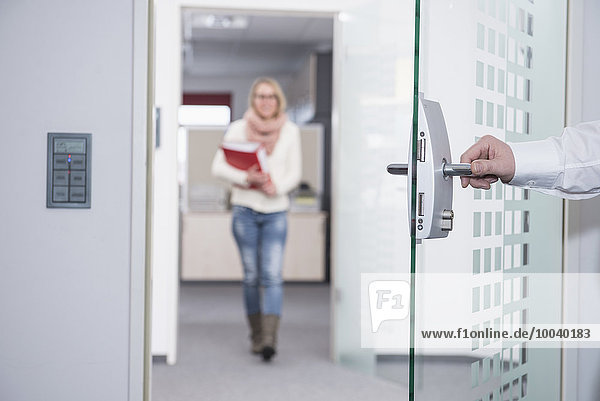 Businessman opening office door for his colleague  Munich  Bavaria  Germany