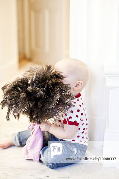 Baby with feather duster