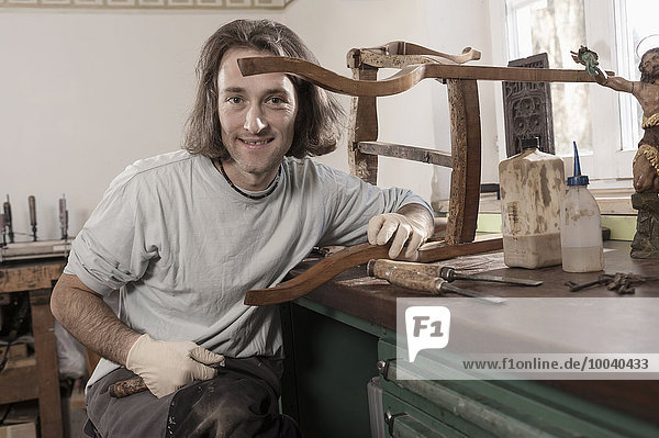 Carpenter repairing an antique wooden chair at workshop  Bavaria  Germany