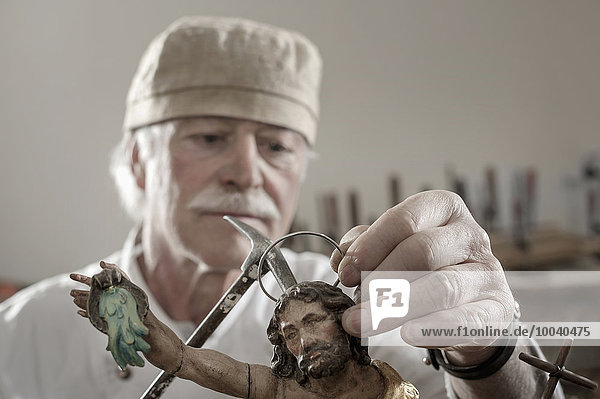 Senior sculptor works on a Jesus Christ statue at workshop  Bavaria  Germany