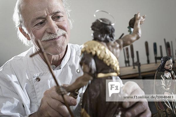 Senior sculptor works on a Jesus Christ statue at workshop  Bavaria  Germany