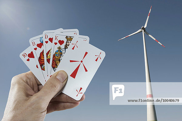 Wind turbine with a man's hand holding playing cards in foreground  Bavaria  Germany