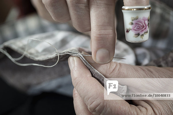 Senior female fashion designer wearing a thimble stitching in workshop  Bavaria  Germany Senior female fashion designer wearing a thimble stitching in workshop, Bavaria, Germany