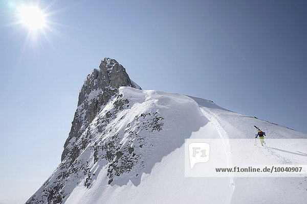Ski mountaineer climbing on snowy peak  Tyrol  Austria