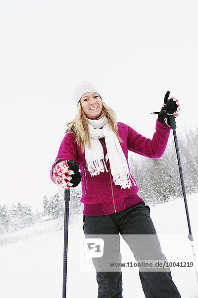 Smiling young woman skiing