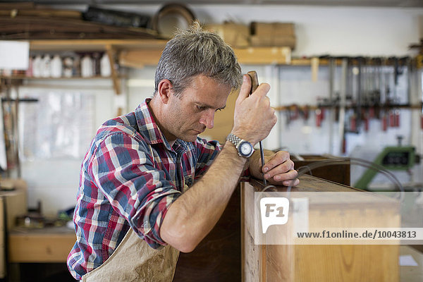 An antique furniture restorer using a handheld work tool and working on the polished top of a piece of furniture.