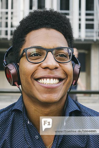 Lächelnder junger Mann mit Kopfhörer im Freien