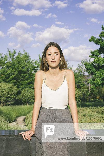 Junge Frau auf einer Wand sitzend