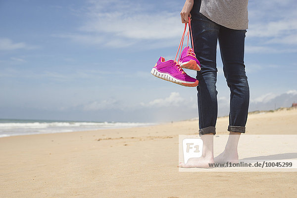 Portugal  Faro  Barfußfrau am Strand mit ihren rosa Turnschuhen